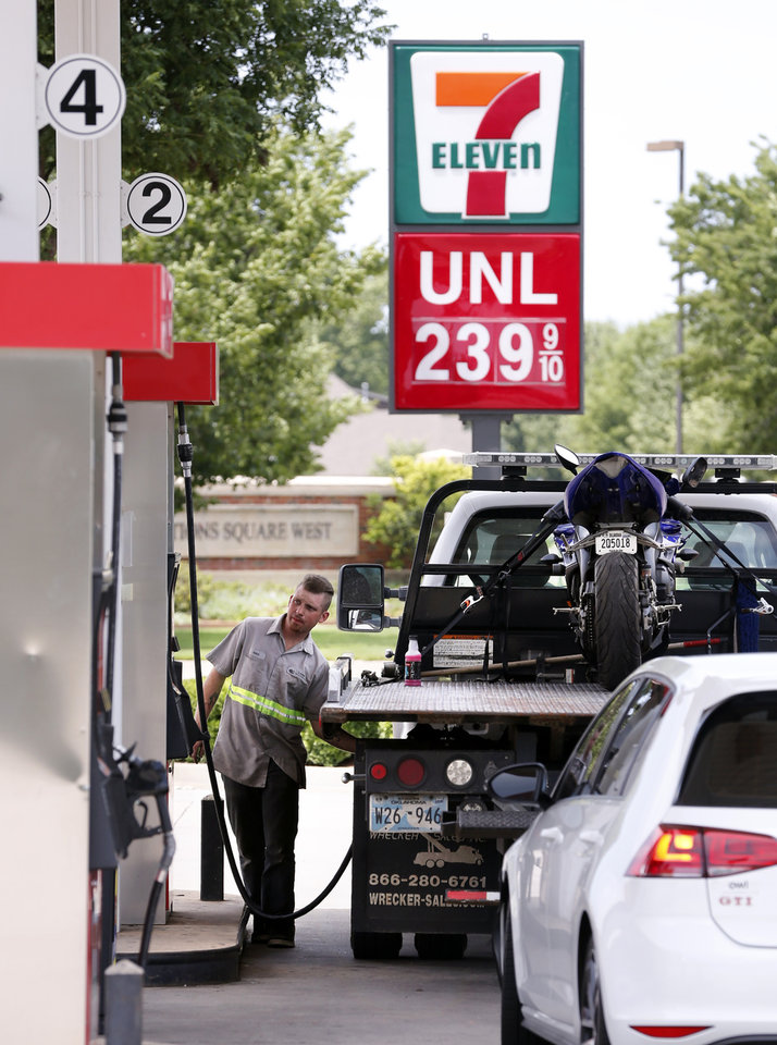 Photo -  Motorists gas up at pumps in Norman on Thursday. Oklahomans are paying more to fill up this year than they did during last year's summer driving season. [Photo by Steve Sisney, The Oklahoman]