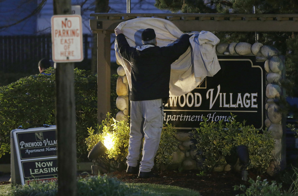 Photo - The sign for the Pinewood Village apartment complex is covered with a sheet, Monday, April 22, 2013, in Federal Way, Wash., where an overnight shooting left five people dead, including a suspect who was shot by arriving officers, police said early Monday. (AP Photo/Ted S. Warren)