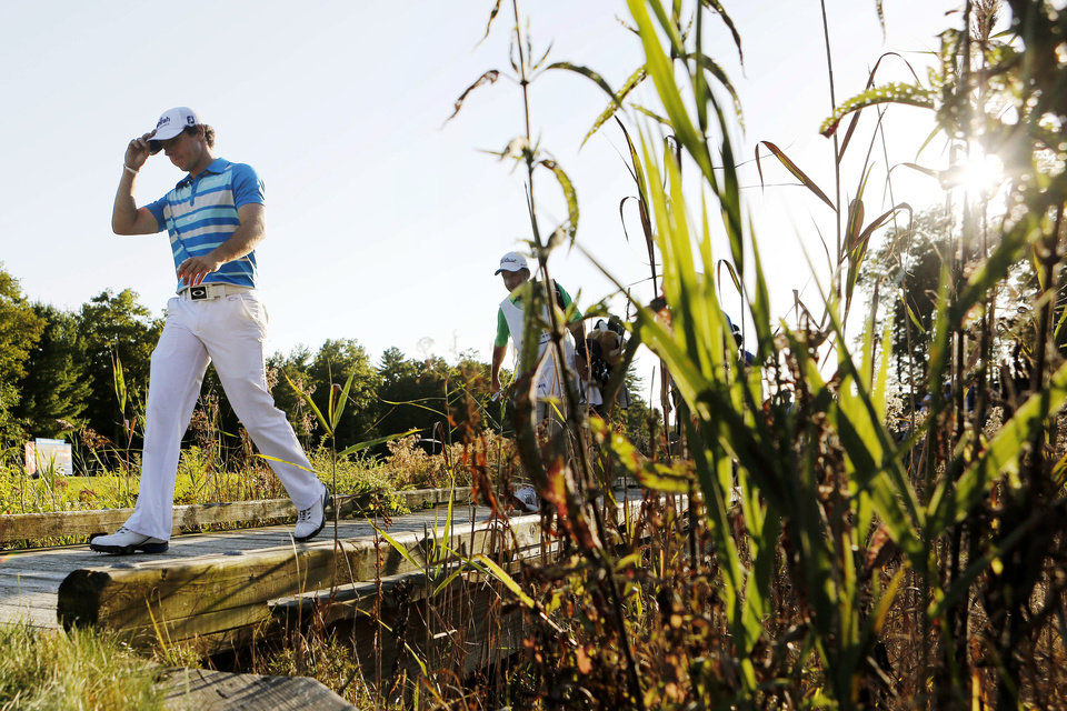 Photo -   Rory McIlroy, left, of Northern Ireland, walks onto the 18th green during the final round of the Deutsche Bank Championship PGA golf tournament at TPC Boston in Norton, Mass., Monday, Sept. 3, 2012. McIlroy won the tournament. (AP Photo/Michael Dwyer)