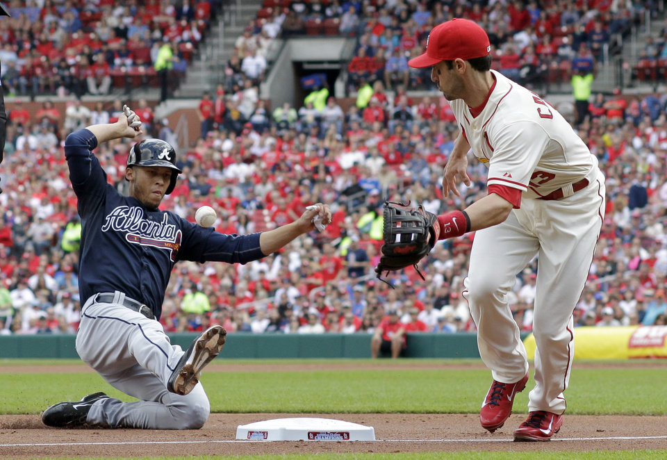 Photo - Atlanta Braves' Andrelton Simmons, left, is safe at third as the throw gets away from St. Louis Cardinals third baseman Matt Carpenter during the second inning of a baseball game Saturday, May 17, 2014, in St. Louis. Simmons was able go on to score and Cardinals second baseman Kolten Wong was charged with a throwing error on the play. (AP Photo/Jeff Roberson)