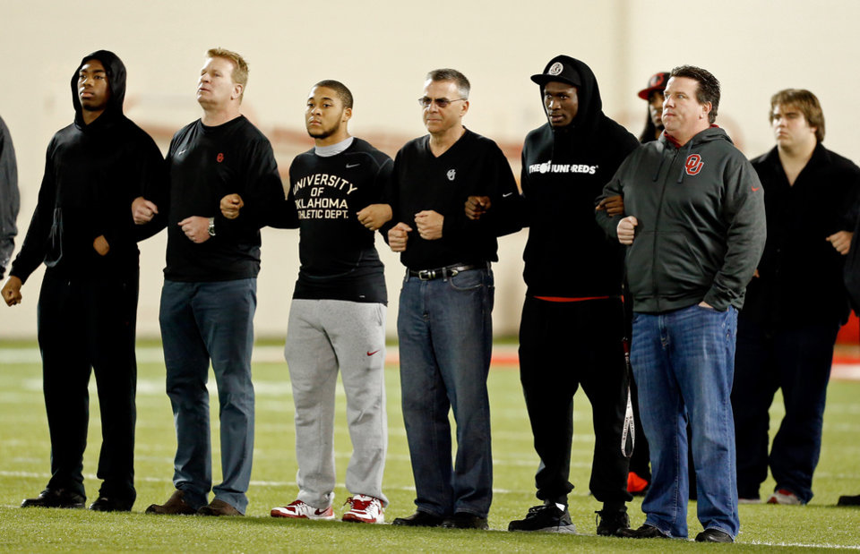Photo - Members and coaches of the University of Oklahoma (OU) Sooner football team surprised the media assembled to cover practice by marching arm in arm, dressed in black into the Everest Practice facility.  The team formed into ranks in the center of the field and stood silently for minutes and then left the facility for the day.The gesture was apparently in response to the day's events surrounding racist comments made by an OU fraternity.   Photo by Steve Sisney, The Oklahoman