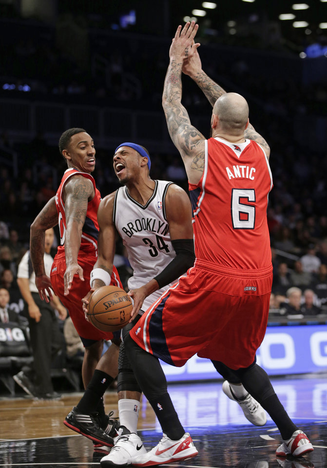 Photo - Brooklyn Nets forward Paul Pierce (34 reacts as Atlanta Hawks point guard Jeff Teague (0) fouls him with Atlanta Hawks center Pero Antic (6) defending beneath the Nets basket in the first half of their NBA basketball game at the Barclays Center, Monday, Jan. 6, 2014, in New York. (AP Photo/Kathy Willens)