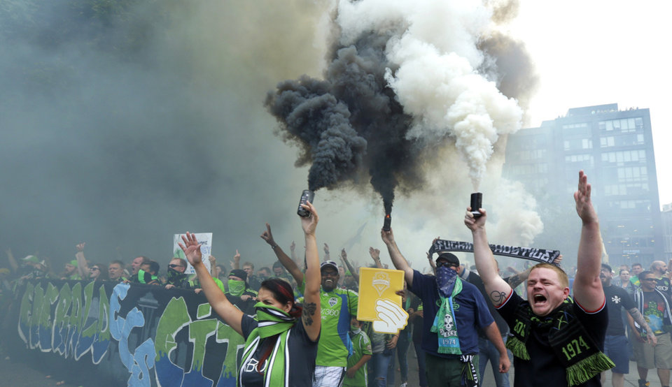 Photo - Seattle Sounders supporters burn smoke devices during the traditional