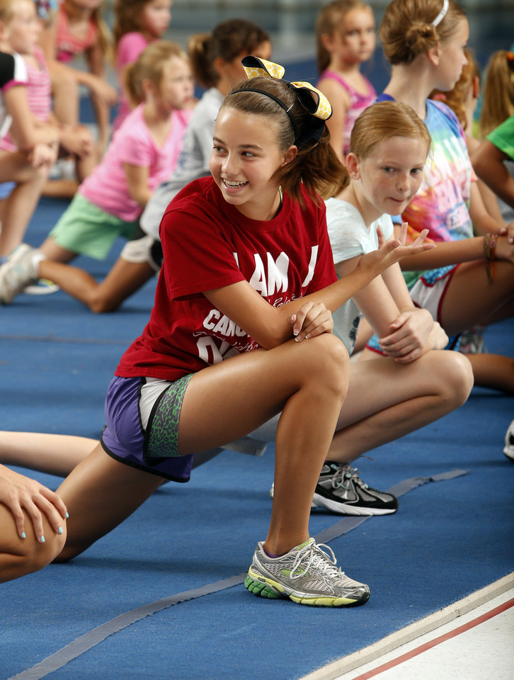 Photo - Taylor Woodin, 12, stretches before drills at a cheer and tumbling camp Wednesday sponsored by the Parks and Recreation Department in Norman. PHOTO BY STEVE SISNEY, THE OKLAHOMAN  STEVE SISNEY