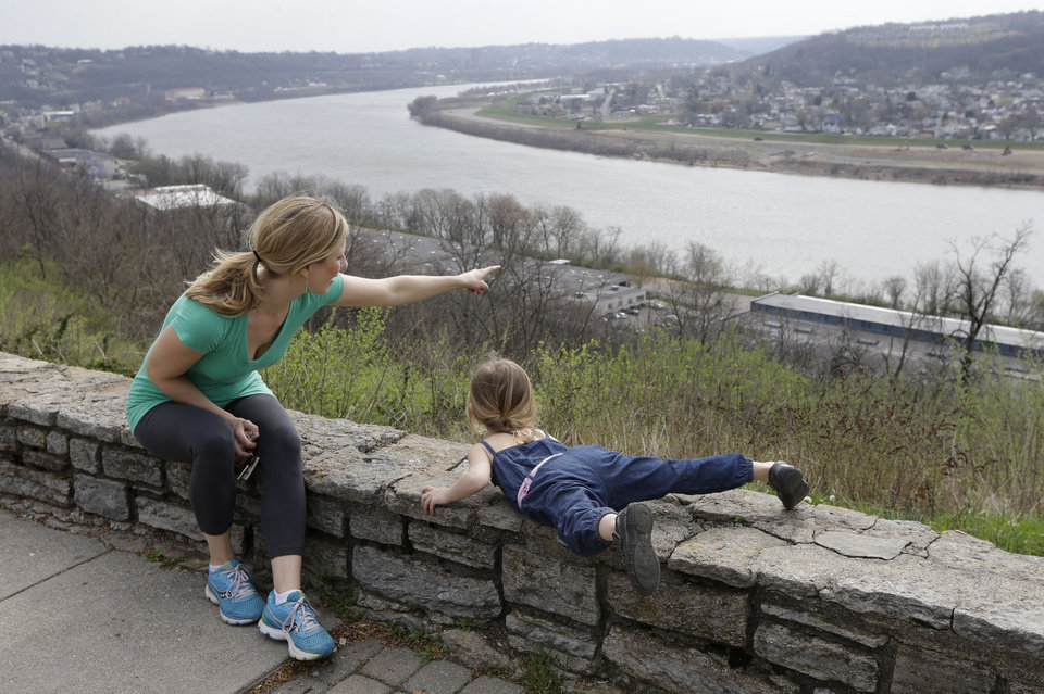 Photo - This April 10, 2013 photo shows Rachel Mardis pointing out over the Ohio River towards northern Kentucky with her daughter Skylar, 2, at the Eden Park Overlook in Cincinnati. A beautiful stroll in Cincinnati begins in lovely Eden Park and ends atop Mount Adams. (AP Photo/Al Behrman)