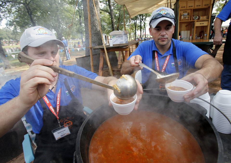 Photo - Spencer Grace, left, and Aaron Ghaemi dish out bowls of Italian duck soup during school day of the Oklahoma Wildlife Expo at the Lazy E Arena and Ranch in Guthrie, OK, Friday, September 28, 2012,  By Paul Hellstern, The Oklahoman