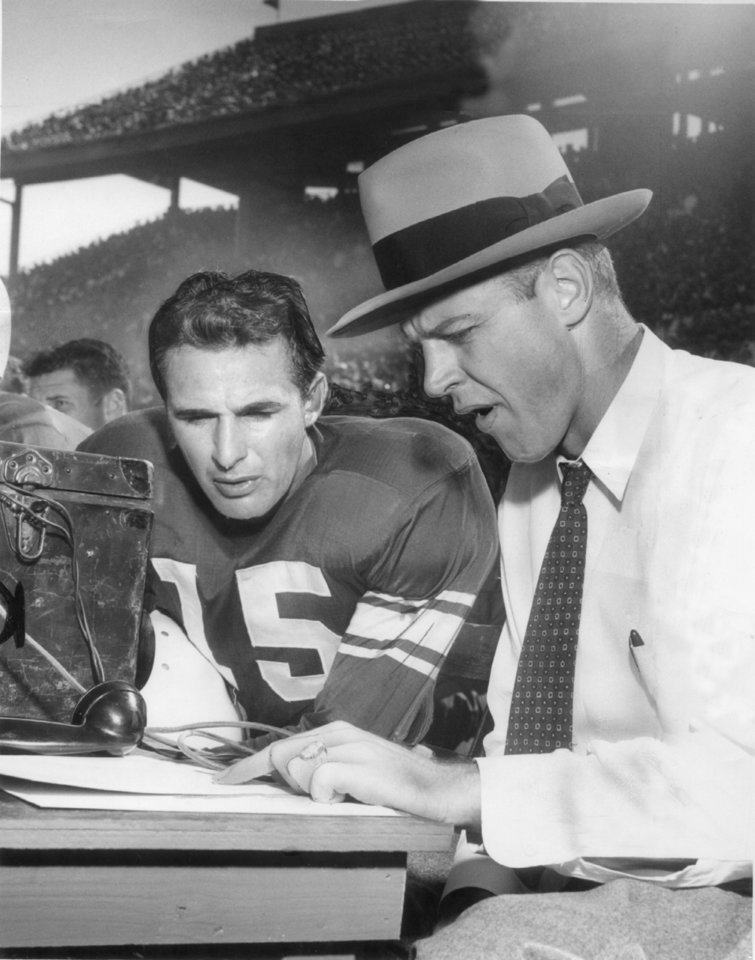 Photo - OU head coach Bud Wilkinson plots game strategy with quarterback Claude Arnold during a game in 1950. (Oklahoma Archives)
