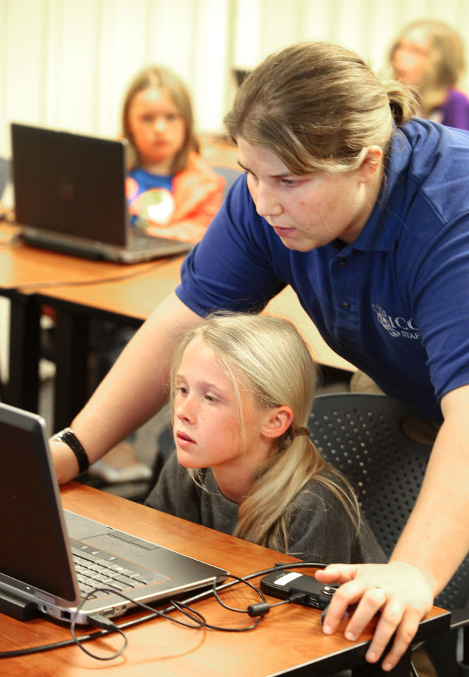 Photo - Girl Scout Junior Esther White, of Troop 234, gets a lesson in Photoshop from instructor Brittany Delgado during a digital photography class.  Photos By David McDaniel,  The Oklahoman