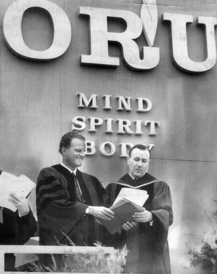 """Photo - DEDICATION: Rev. Billy Graham and Evangelist Dr. Oral Roberts dedicate the new Oral Roberts University.  """"Evangelist Billy Graham issued a clarion call for Christian education Sunday as the dedicatory speaker for new Oral Roberts University in Tulsa.  The university was dedicated before a throng of some 18,000 persons who came from all over the world to witness the event.  It was a colorful ceremony with presidents, faculty members and alumni representatives of 132 colleges and universities in the United States taking part in the processional line of march.""""  Photo was taken 4/2/67 and appeared in the 4/3/67 Daily Oklahoman."""