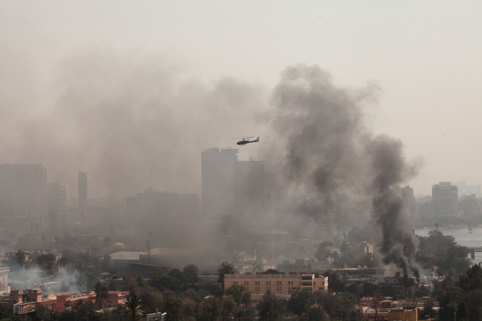 Photo - Smoke rises from the Police Officers Club, left, and the Egyptian Soccer Federation, right, as a police helicopter surveys the scene after protesters set fire following a court verdict in Saturday, March 9, 2013. Fans of Cairo's Al-Ahly club have stormed Egypt's soccer federation headquarters, set it ablaze after a court acquitted seven of nine police official on trial for their alleged part in deadly stadium melee. A fire also broke out Saturday in a nearby police club, but it was not immediately known whether Al-Ahly fans started the blaze there too. (AP Photo/Maya Alleruzzo)