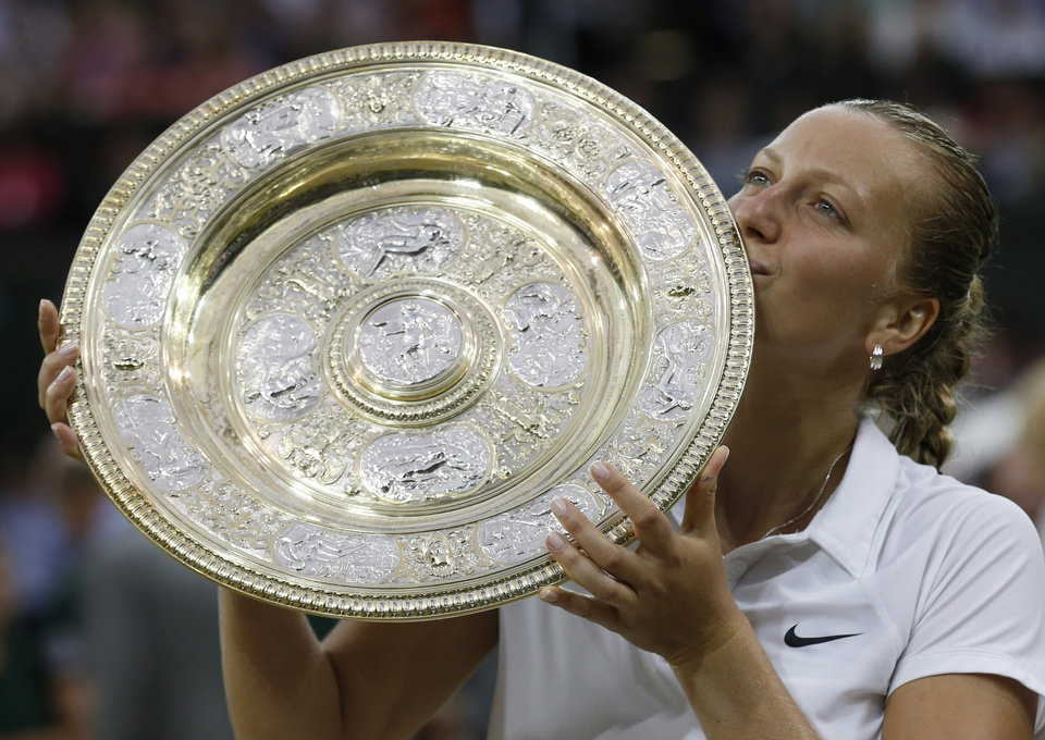 Photo - Petra Kvitova of Czech Republic kisses the trophy after winning the women's singles final against Eugenie Bouchard of Canada at the All England Lawn Tennis Championships in Wimbledon, London, Saturday July 5, 2014. (AP Photo/Sang Tan)
