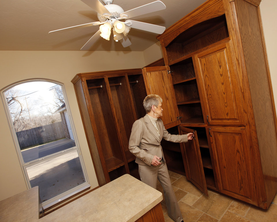 Real estate agent Mary Berry  shows some of the features of a laundry room/office in her listing at 13504 Calistoga Drive in Oklahoma City, Friday, Dec. 30, 2011. Photo by Nate Billings, The Oklahoman