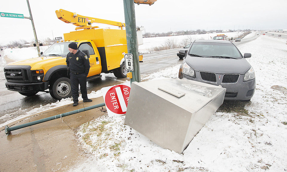 Photo - A driver lost control Monday on the ice and snow and ran over the traffic signal control box at the end of the northbound exit ramp from the Lake Hefner Parkway at Hefner Road in Oklahoma City.  Photo by Paul B. Southerland, The Oklahoman