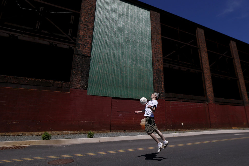 Photo - Simon Collum, 35, of Ridgewood, N.J., plays soccer near a warehouse adjacent to Red Bull Arena before the start of an international soccer friendly between Turkey and the United States, Sunday, June 1, 2014, in Harrison, N.J. (AP Photo/Julio Cortez)