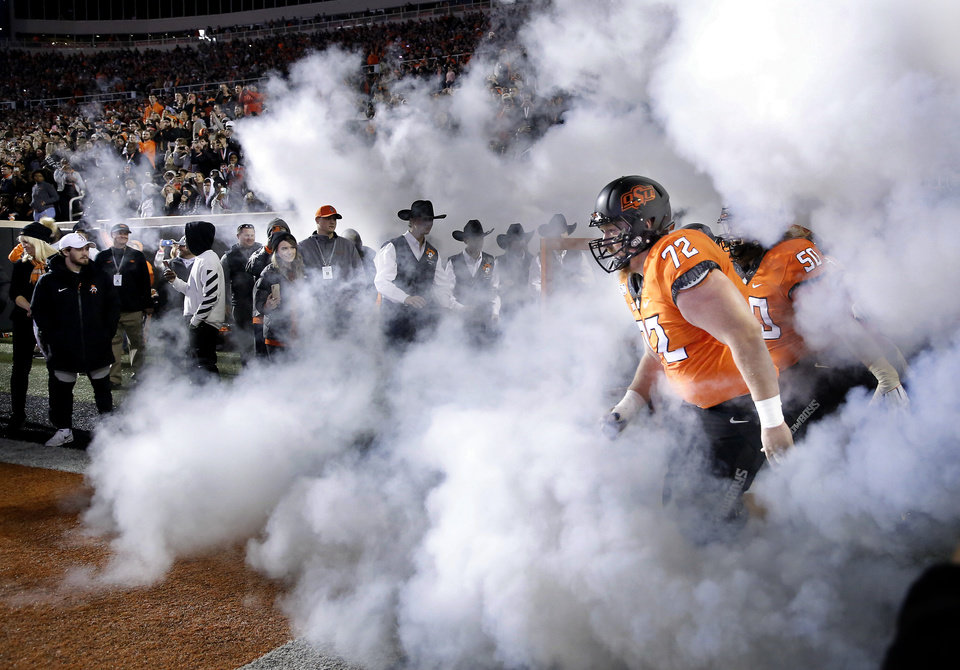 Photo - Oklahoma State's Johnny Wilson (72) runs onto the field before the Bedlam college football game between the Oklahoma State Cowboys (OSU) and Oklahoma Sooners (OU) at Boone Pickens Stadium in Stillwater, Okla., Saturday, Nov. 30, 2019. OU won  34-16. [Sarah Phipps/The Oklahoman]
