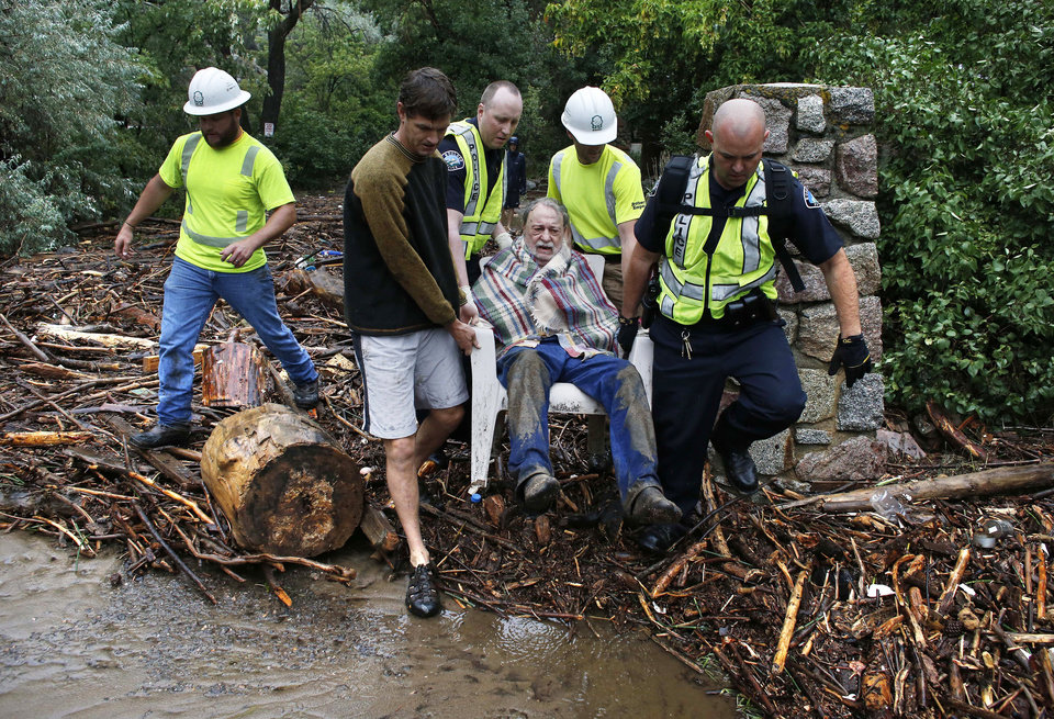 Photo - Will Pitner is rescued by emergency workers, and neighbor Jeff Writer, left, after a night trapped sheltering outside on high ground above his home as it filled with water from a surge of water, after days of record rain and flooding, at the base of Boulder Canyon, Colo., Friday Sept. 13, 2013 in Boulder. Flash flooding in Colorado has left at least three people reportedly dead and the widespread high waters have hampered emergency workers' access to affected communities as heavy rains hammered northern Colorado. (AP Photo/Brennan Linsley)