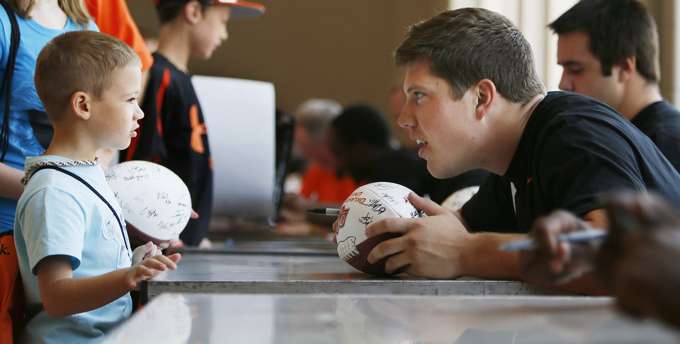 Photo - Oklahoma State football player Cooper Bassett, right,  talks with fan Colin Schaller, 7, of Stillwater, during OSU Fan Appreciation Day at Gallagher-Iba Arena in Stillwater, Okla., Saturday, Aug. 4, 2012. Photo by Nate Billings, The Oklahoman