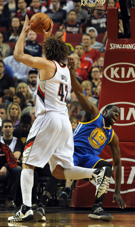 Photo - Portland Trail Blazers center Robin Lopez (42) is called for charging as he runs into Golden State Warriors forward Draymond Green (23) during the first half of an NBA basketball game in Portland, Ore., Sunday, April 13, 2014. (AP Photo/Steve Dykes)