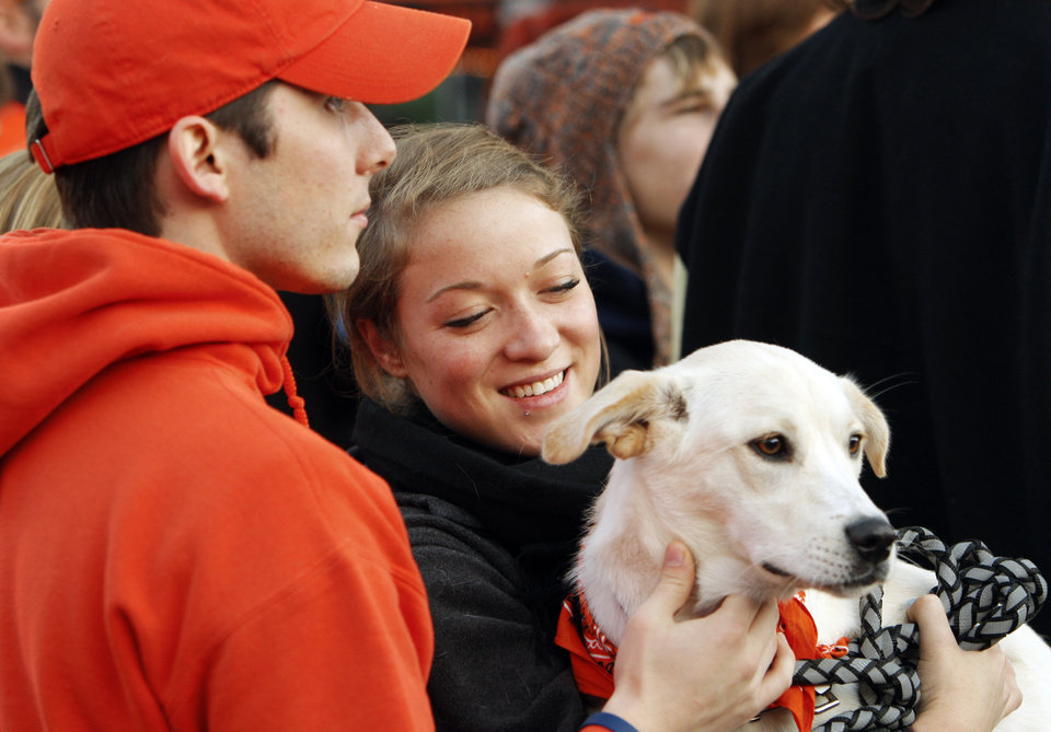 Photo - OSU student Louise Ivers, of Cape Girardeau, Mo., holds Lola as fellow student Brock Colombine, of Okmulgee, Okla., pets the dog while waiting for the Spirit Walk before the Bedlam college football game between the Oklahoma State University Cowboys (OSU) and the University of Oklahoma Sooners (OU) at Boone Pickens Stadium in Stillwater, Okla., Saturday, Dec. 3, 2011. Photo by Nate Billings, The Oklahoman