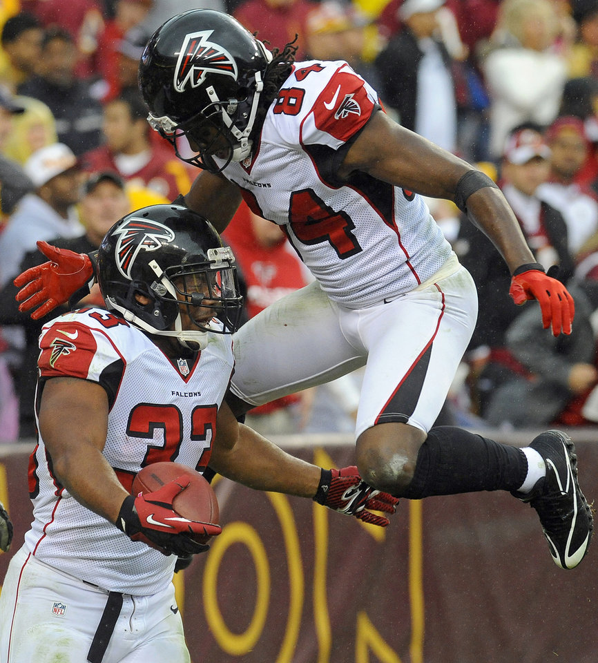 Photo -   Atlanta Falcons running back Michael Turner (33) celebrates his touchdown with teammate wide receiver Roddy White (84) during the second half of an NFL football game against the Washington Redskins in Landover, Md., Sunday, Oct. 7, 2012. (AP Photo/Richard Lipski)