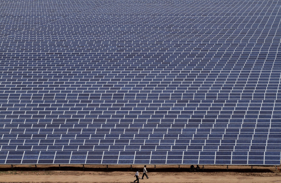 Photo - FILE - In this Saturday, April 14, 2012, file photo, Indian workers walk past solar panels at the Gujarat Solar Park at Charanka in Patan district, about 250 kilometers (155 miles) from Ahmadabad, India. In the 2000s, large investors in so-called clean technology wanted to finance companies that would help eliminate the world's dependence on oil, natural gas and coal. But in 2013, clean technology investment funds are not trying to replace the fossil fuel industry, they're trying to help it by financing companies that can make mining and drilling less dirty. (AP Photo/Ajit Solanki,File) ORG XMIT: NYBZ563