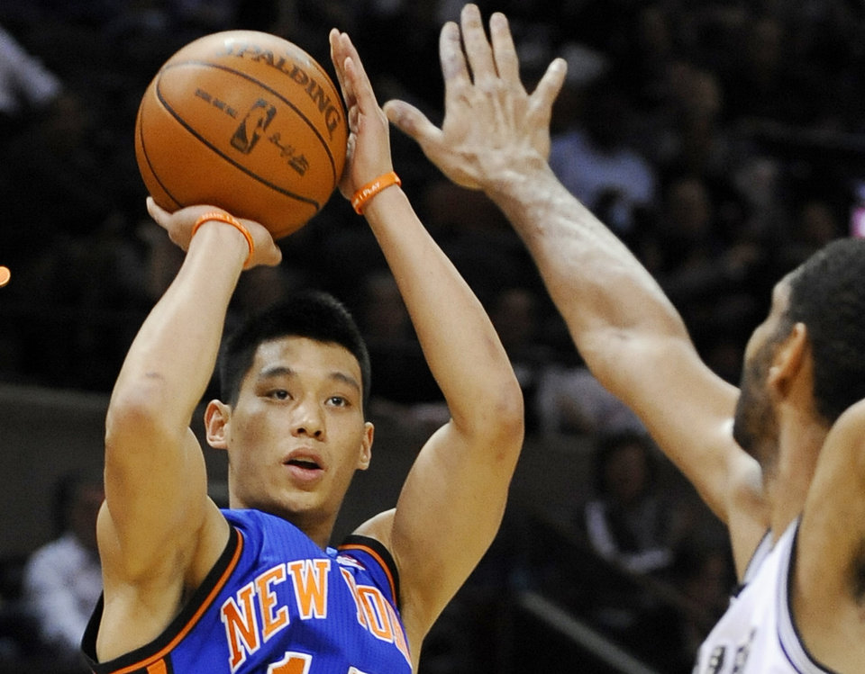 Photo -   FILE - In this March 7, 2012 file photo, New York Knicks' Jeremy Lin, left, shoots over San Antonio Spurs' Tim Duncan during the first half of an NBA basketball game, in San Antonio. This would have been such an easy decision in February. Lin was the biggest thing in basketball, and no way the Knicks would have let him go elsewhere. Now, knowing his price and with no assurance he'll play as he did when Linsanity reigned, the Knicks may allow Lin to leave for Houston. (AP Photo/Darren Abate, File)