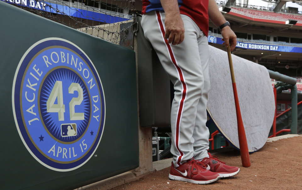 Photo - A Philadelphia Phillies coach stands next to a sign honoring Jackie Robinson day prior to a baseball game against the Cincinnati Reds, Monday, April 15, 2013, in Cincinnati. (AP Photo/Al Behrman)