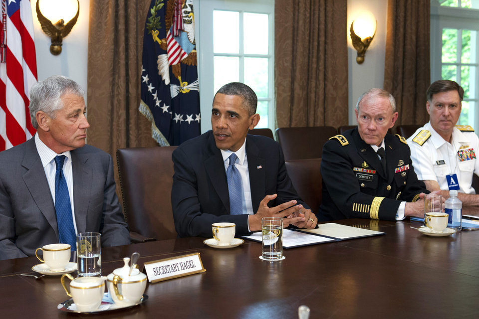 Photo - Defense Secretary Chuck Hagel, left, listens to President Barack Obama, next to Joint Chiefs Chairman Gen. Martin Dempsey, and Vice Chief of Naval Operations Adm. Mark Ferguson, during a meeting of service secretaries, service chiefs, and senior enlisted advisers to discuss sexual assault in the military in the Cabinet Room of the White House in Washington, Thursday, May 16, 2013. (AP Photo/Jacquelyn Martin)