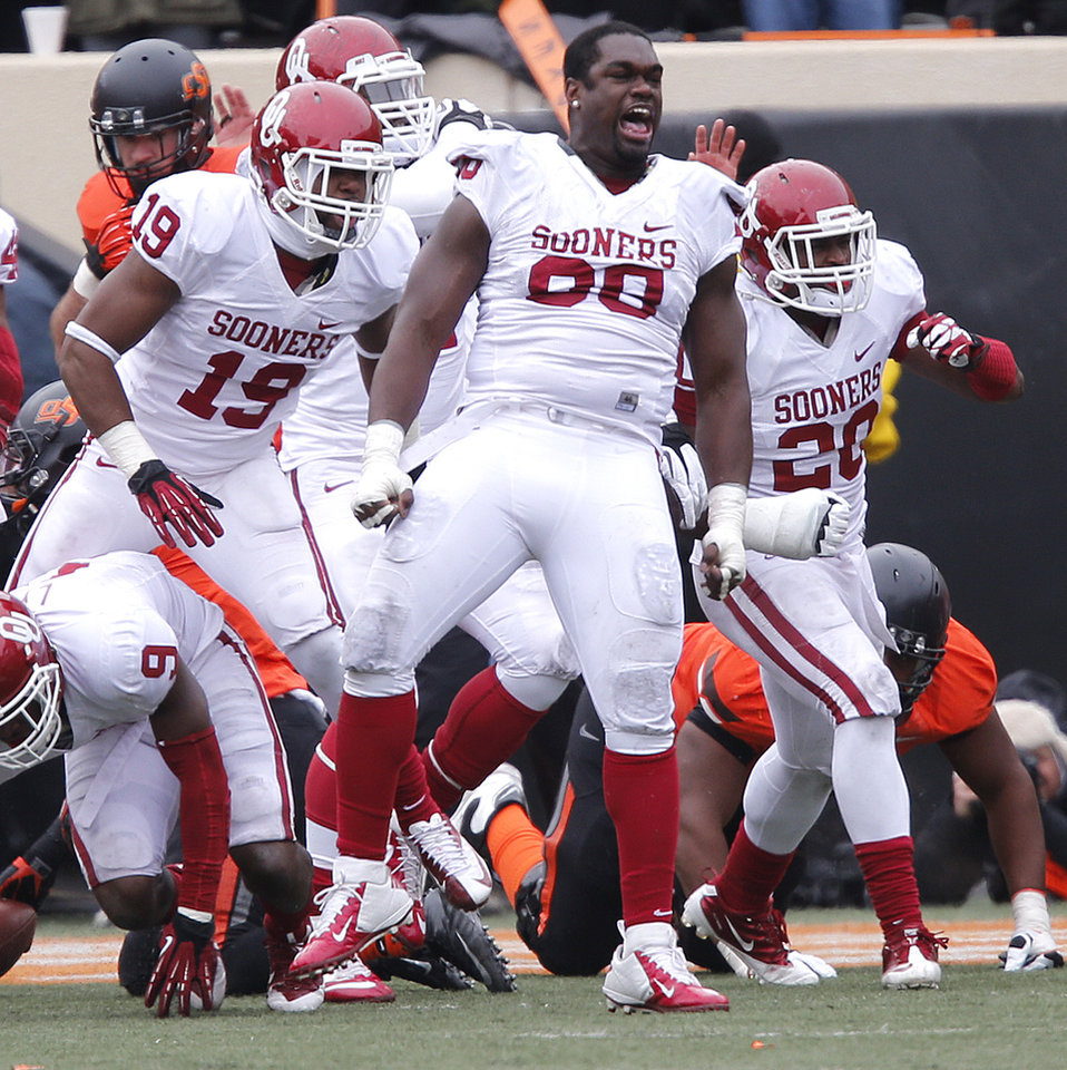 Photo - Oklahoma's Chuka Ndulue (98) reacts after stoping Oklahoma State on fourth and goal during the Bedlam college football game between the Oklahoma State University Cowboys (OSU) and the University of Oklahoma Sooners (OU) at Boone Pickens Stadium in Stillwater, Okla., Saturday, Dec. 7, 2013. Photo by Chris Landsberger, The Oklahoman