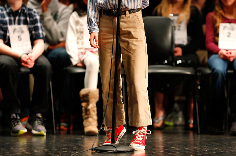 Photo -  A contestant stands on his toes to reach the microphone during a Scripps Regional Spelling Bee at John Marshall High School in Oklahoma City, Wednesday, Jan., 23, 2013.