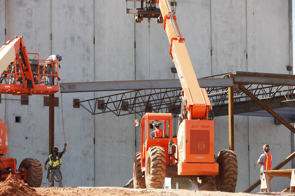 Workers lift the last piece of structural steel for the Deer Creek Performing Arts and Athletic Center.