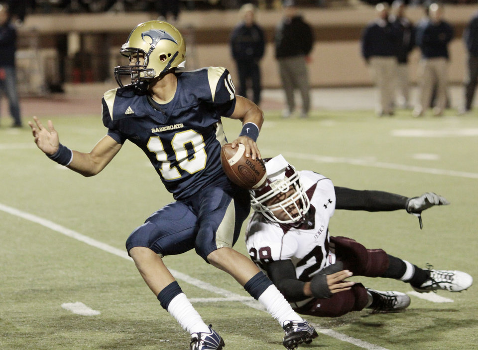 Photo - HIGH SCHOOL FOOTBALL PLAYOFFS: SM quarterback Kendal Thompson (10) avoids JHS's Alex Ross (28) during the high school semifinal playoff football game between Southmoore and Jenks at Putnam City Stadium Saturday, Nov. 28, 2009. Photo by Doug Hoke, The Oklahoman  ORG XMIT: KOD