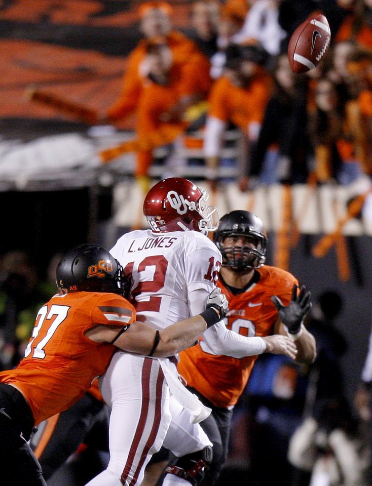 Photo - Oklahoma's Landry Jones (12) is hit by Oklahoma State's Alex Elkins (37) as he fumbles during the Bedlam college football game between the Oklahoma State University Cowboys (OSU) and the University of Oklahoma Sooners (OU) at Boone Pickens Stadium in Stillwater, Okla., Saturday, Dec. 3, 2011. Photo by Bryan Terry, The Oklahoman