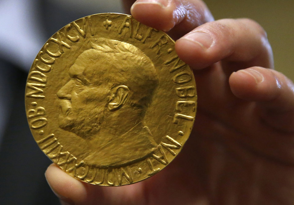 Photo - Bidder Ole Bjorn Fausa, of Norway, holds the 1936 Nobel Peace Prize in Baltimore, Thursday, March 27, 2014, the second Nobel Peace Prize ever to come to auction. It was won by an anonymous telephone bidder for $950,000. The recipient was Argentina's foreign minister, Carlos Saavedra Lamas, who was honored for his role in negotiating the end of the Chaco War between Paraguay and Bolivia. (AP Photo/Patrick Semansky)