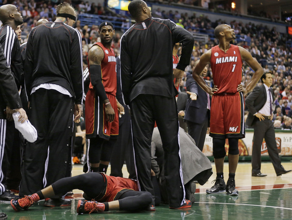 Photo - CORRECTS SPELLING TO DWYANE, INSTEAD OF DWAYNE - Miami Heat's Dwyane Wade lies on the court during the first half against the Milwaukee Bucks in an NBA basketball game Friday, March 15, 2013, in Milwaukee. (AP Photo/Jeffrey Phelps)