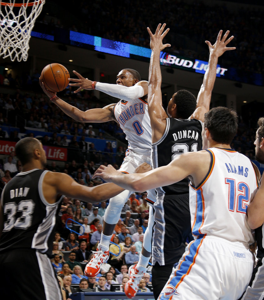 Photo - /tokcon/ goes to the basket past San Antonio's Tim Duncan (21) during an NBA basketball game between the Oklahoma City Thunder and the San Antonio Spurs at Chesapeake Energy Arena in Oklahoma City, Thursday, April 3, 2014. Photo by Bryan Terry, The Oklahoman