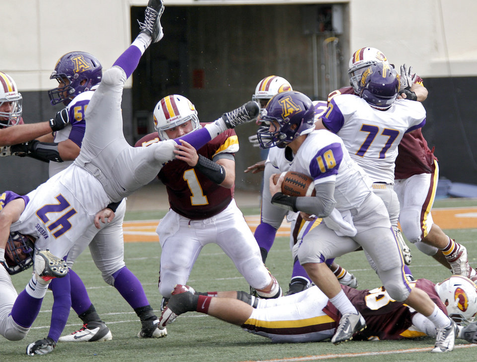 Anadarko's Kris Whitfield (42) is upended as Brandon Pollard (18) looks for running room past the Clinton defense during the Class 4A Oklahoma state championship football game between Anadarko and Clinton at Boone Pickens Stadium on Saturday, Dec. 1, 2012, in Stillwater, Okla.   Photo by Chris Landsberger, The Oklahoman