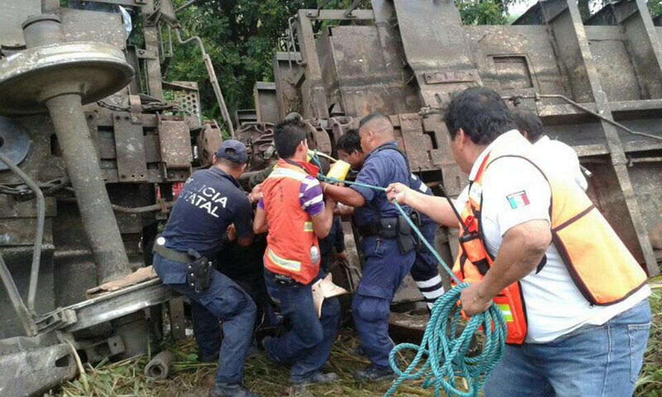 Photo - In this photo release by the Civil Protection of the State of Tabasco, police agents and rescue workers work at a site where a train derailed in Tabasco, Mexico, Sunday, Aug. 25, 2013.  An cargo train known as