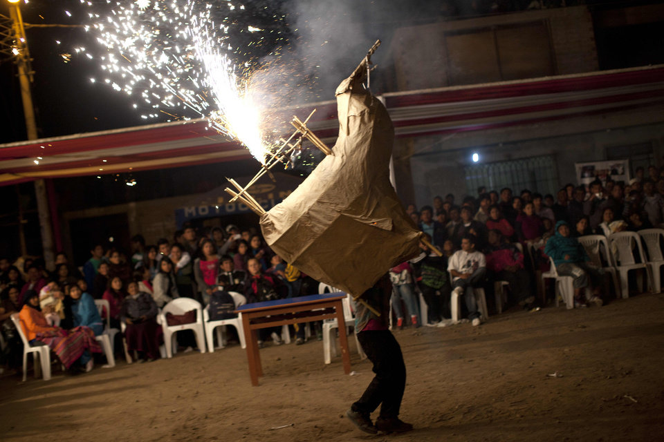 "In this Sept. 23, 2012 photo, a man dances ""La Vaca Loca"" or ""The Crazy Cow"" during festivities in honor of Santa Efigenia in La Quebrada, Peru. Every year, Peruvians descended from African slaves come to La Quebrada to celebrate the adored black saint Santa Efigenia, the only African saint venerated in Peru. A chapel was built in La Quebrada in the 18th century dedicated to Santa Efigenia, who was popular among the then Spanish colony's African slaves. Cat races, a fireworks dance and a night of eating and drinking close out the celebration. (AP Photo/Rodrigo Abd)"
