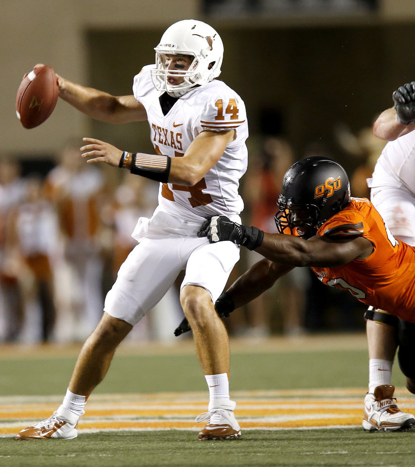 Oklahoma State\'s Tyler Johnson (40) tries to bring down Texas\' David Ash (14) during a college football game between Oklahoma State University (OSU) and the University of Texas (UT) at Boone Pickens Stadium in Stillwater, Okla., Saturday, Sept. 29, 2012. Photo by Bryan Terry, The Oklahoman