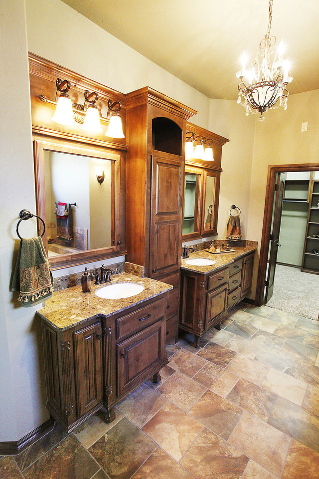 Photo - Double vanities, mirrors and light fixtures are separated by a linen cabinet in the master bath at 12005 Tuscany Ridge.