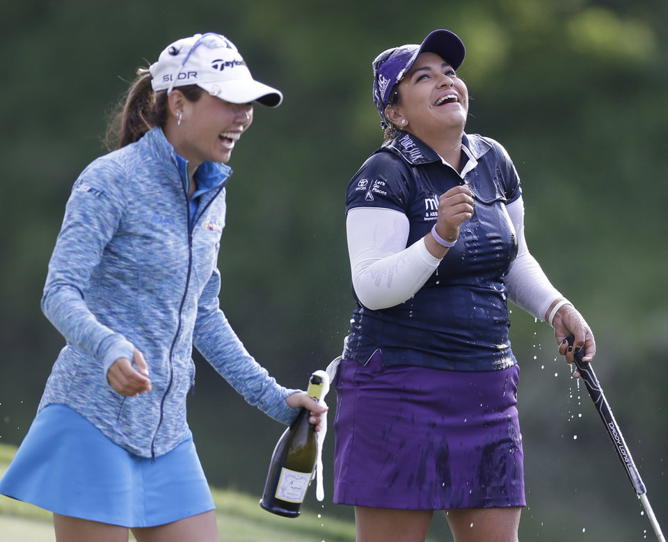Photo - Lizette Salas celebrates winning the Kingsmill Championship golf tournament at the Kingsmill resort  along with fellow golfer Nina Harigae, left, in Williamsburg, Va., Sunday, May 18, 2014.  Salas won her first LPGA event after shooting an even par-71 leaving her at 13-under for the tournament.  (AP Photo/Steve Helber)