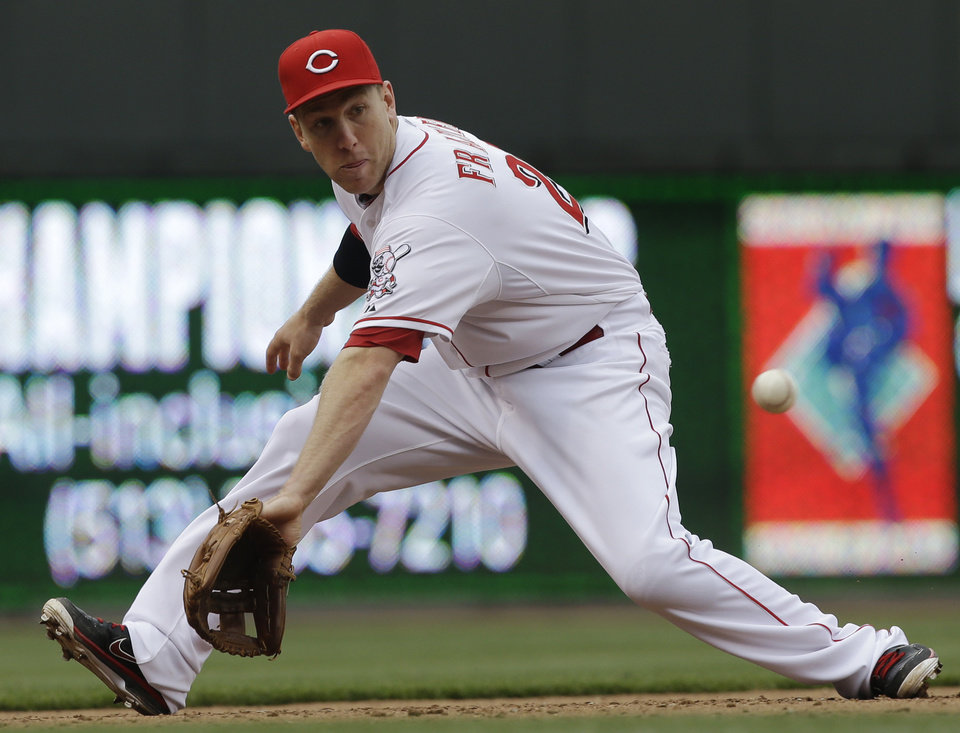 Photo - Cincinnati Reds third baseman Todd Frazier fields a ground ball hit by Chicago Cubs' Starlin Castro in the fifth inning of a baseball game on Saturday, May 25, 2013, in Cincinnati. Frazier threw Castro out at first. (AP Photo/Al Behrman)