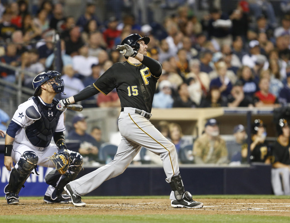Photo - Pittsburgh Pirates' Ike Davis and San Diego Padres catcher Yasmani Grandal watch Davis' towering fly ball with the bases loaded that was caught at the wall  during the third inning of a baseball game Monday, June 2, 2014, in San Diego. The sacrifice fly brought in a run.  (AP Photo/Lenny Ignelzi)