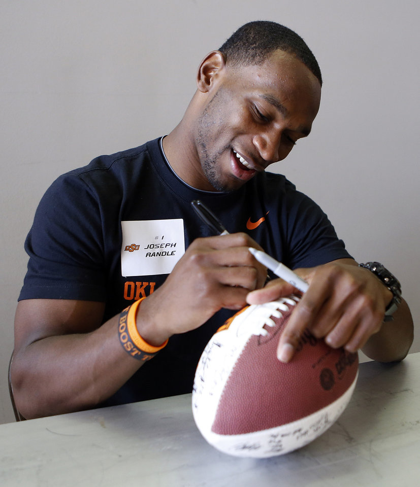 Photo - Joseph Randle signs a football during Oklahoma State's Fan Appreciation Day at Gallagher-Iba Arena in Stillwater, Okla., Saturday, Aug. 4, 2012. Photo by Sarah Phipps, The Oklahoman