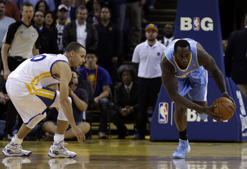 Photo - Denver Nuggets' J.J. Hickson, right, steals the ball from Golden State Warriors' Stephen Curry during the final seconds of an NBA basketball game on Wednesday, Jan. 15, 2014, in Oakland, Calif. (AP Photo/Ben Margot)