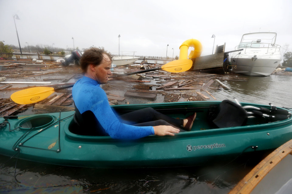 Currie Wagner kayaks through floodwaters on his way to check up on his grandmother Betty Wagner's house, which was destroyed and wound atop the Mantoloking Bridge the morning after superstorm Sandy rolled through, Tuesday, Oct. 30, 2012, in Brick, N.J. Sandy, the storm that made landfall Monday, caused multiple fatalities, halted mass transit and cut power to more than 6 million homes and businesses. (AP Photo/Julio Cortez) ORG XMIT: NJJC120