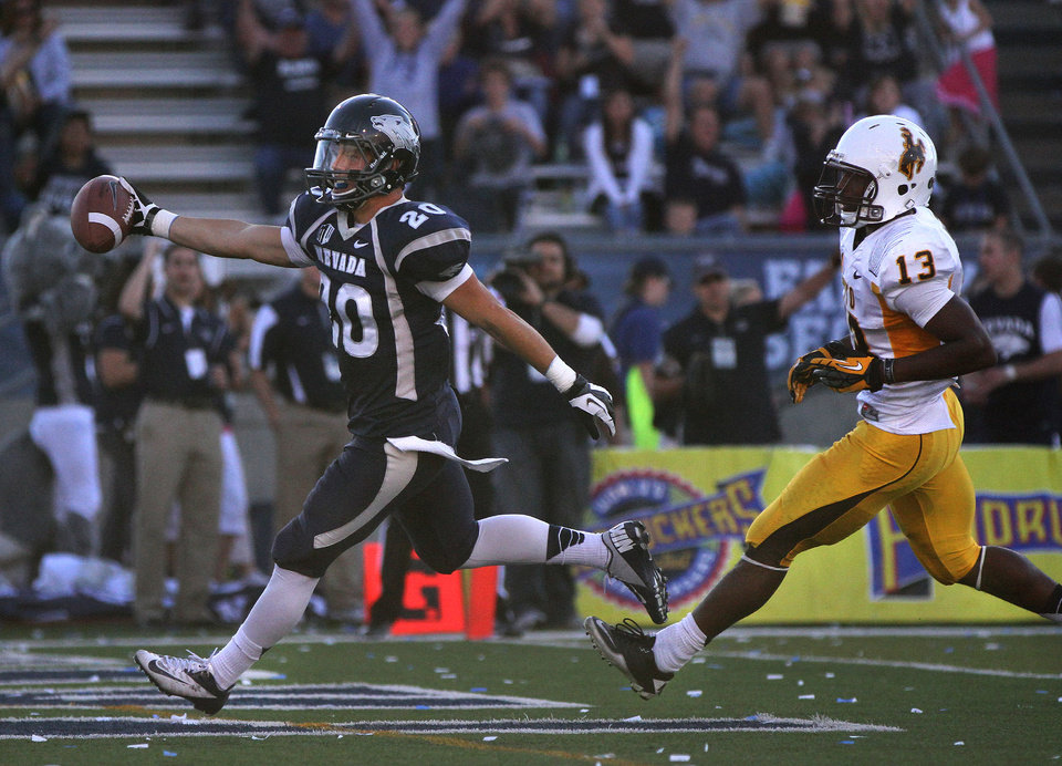 Photo -   Nevada's Kendall Brock (20) runs into the end zone followed by Wyoming's Darrenn White (13) during the first half of an NCAA college football game in Reno, Nev., on Saturday, Oct. 6, 2012. (AP Photo/Cathleen Allison)