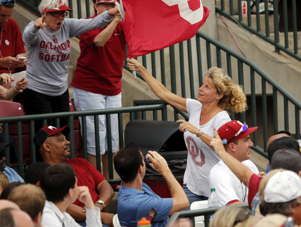 Photo - Women's basketball head coach Sherri Coale carries an OU flag through the stands at the NCAA Super Regional softball game as the University of Oklahoma (OU) Sooners defeats Texas A&M 10-2 at Marita Hines Field on Friday, May 24, 2013 in Norman, Okla. Photo by Steve Sisney, The Oklahoman