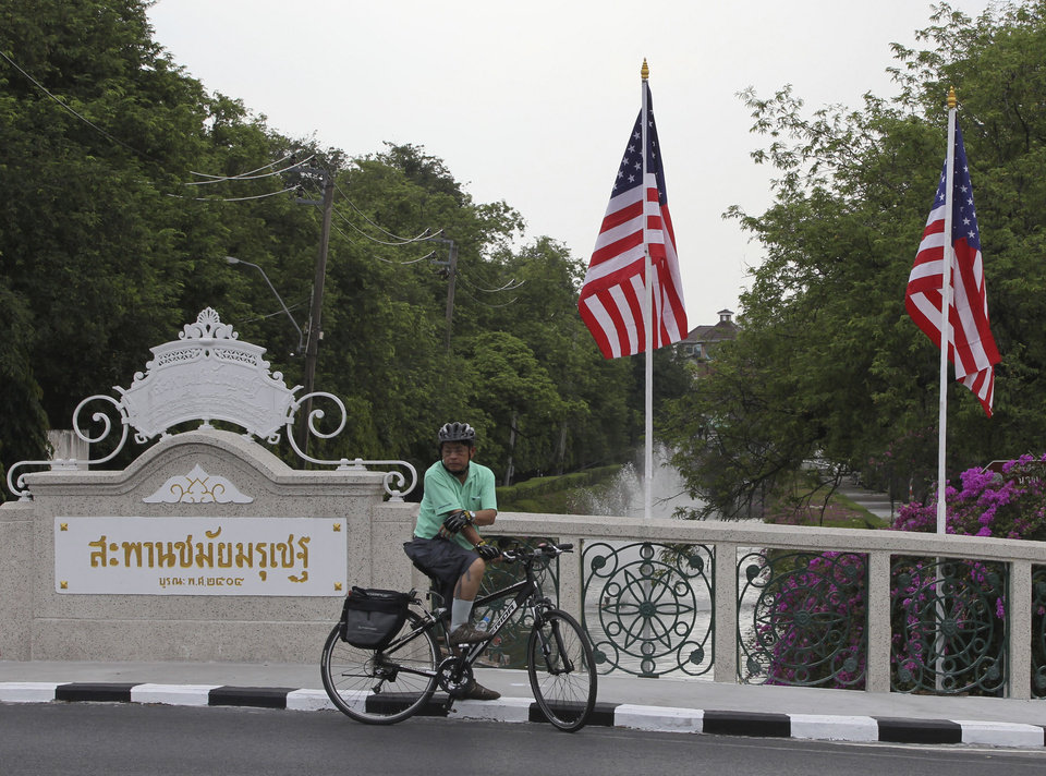 Photo -   A cyclist waits for the traffic on a bridge decorated with US flags outside the government house in Bangkok, Thailand Saturday, Nov. 17, 2012. Obama will arrive in Thailand on Sunday, Nov. 18, 2012 as part of his southeast Asian nations tour which includes Myanmar and Cambodia. (AP Photo/Apichart Weerawong)